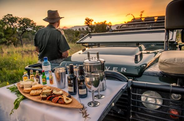 Sundowners at a scenic spot in the bush during a game drive.
